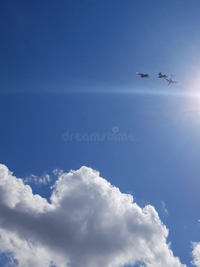 Twee zeemeeuwen op een de zomer bewolkte dag in de hemel vliegen samen achter het vliegtuig stock afbeeldingen