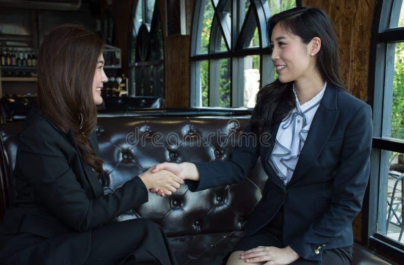 Twee zekere Aziatische het bedrijfsvrouw schudden handen tijdens een vergadering in het bureau royalty-vrije stock foto's