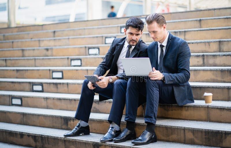 Twee zekere bedrijfsmensen die op treden zitten die laptop in stedelijke stad bekijken royalty-vrije stock afbeelding
