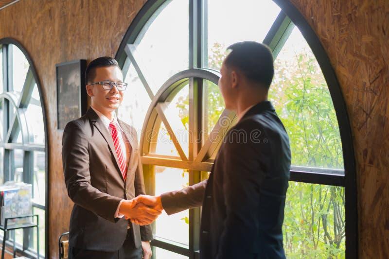 Twee zekere zakenman het schudden handen voor het aantonen van hun overeenkomst om overeenkomst of contract tussen hun firma's te stock afbeelding