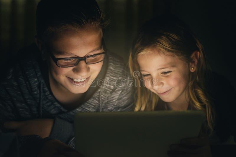 Twee zoete jonge geitjes die op een Tabletpc spelen stock foto's