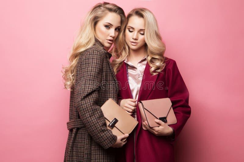 Twee zoete jonge vrouwen die in aardige kleren, laag, handtas stellen Zusters, tweelingen De foto van de de lentemanier stock afbeeldingen