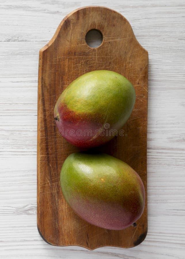 Twee zoete mango's op rustieke houten raad over witte houten oppervlakte, hoogste mening Vlak leg hierboven, van, overheadkosten  royalty-vrije stock afbeelding