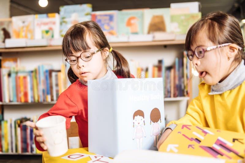 Twee zonnige kinderen die blije het leren brieven voelen en het lezen van boeken stock foto's