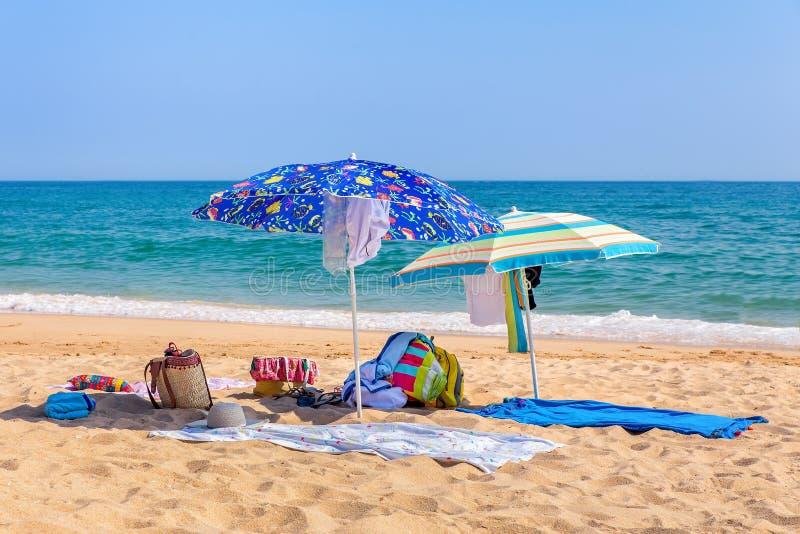 Twee zonparaplu's en strandlevering op zee royalty-vrije stock afbeelding