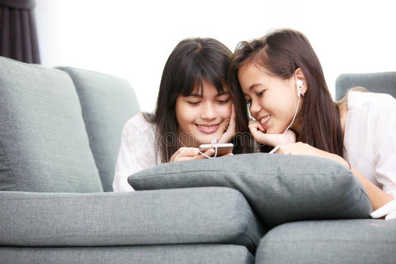 Twee zuster Aziatisch meisje die smarthphone samen bekijken stock foto