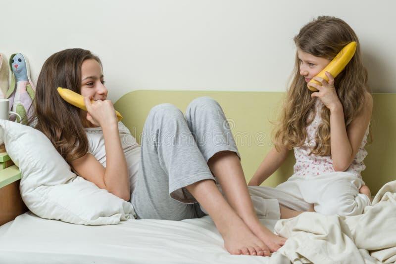 Twee zusterkinderen in pyjama'sspel in de ochtend in bed stock afbeeldingen
