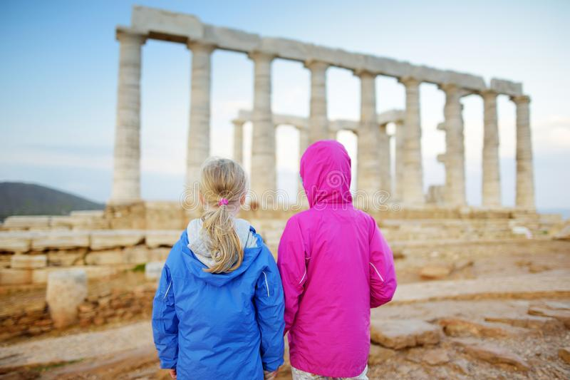 Twee zusters die de Oude Griekse tempel van Poseidon onderzoeken bij Kaap Sounion, één van de belangrijkste monumenten van de Gou stock foto