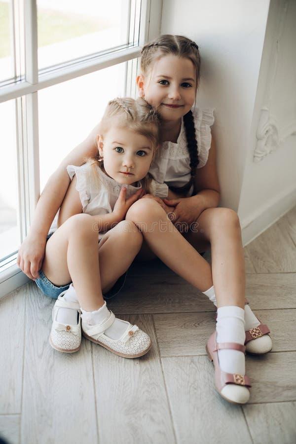 Twee zusters die dichtbij venster zitten en elkaar koesteren royalty-vrije stock foto's