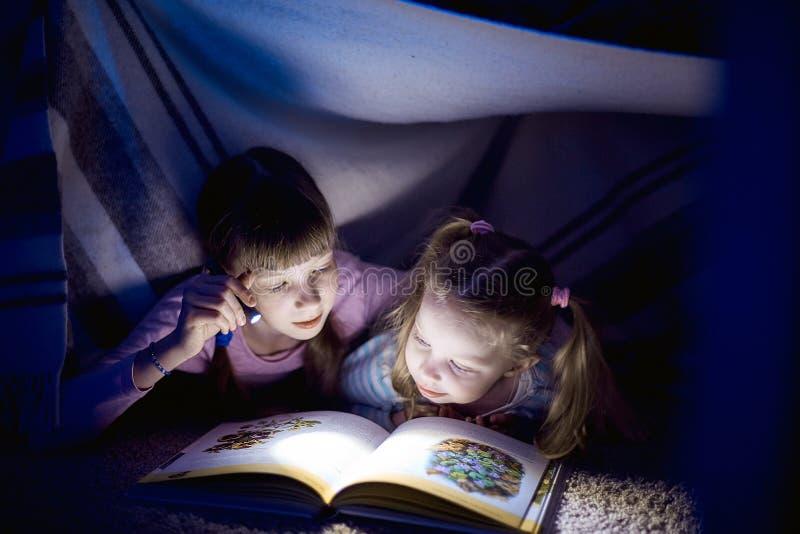 Twee zusters die een boek met een flitslicht in een donkere ruimte lezen bij nacht royalty-vrije stock fotografie