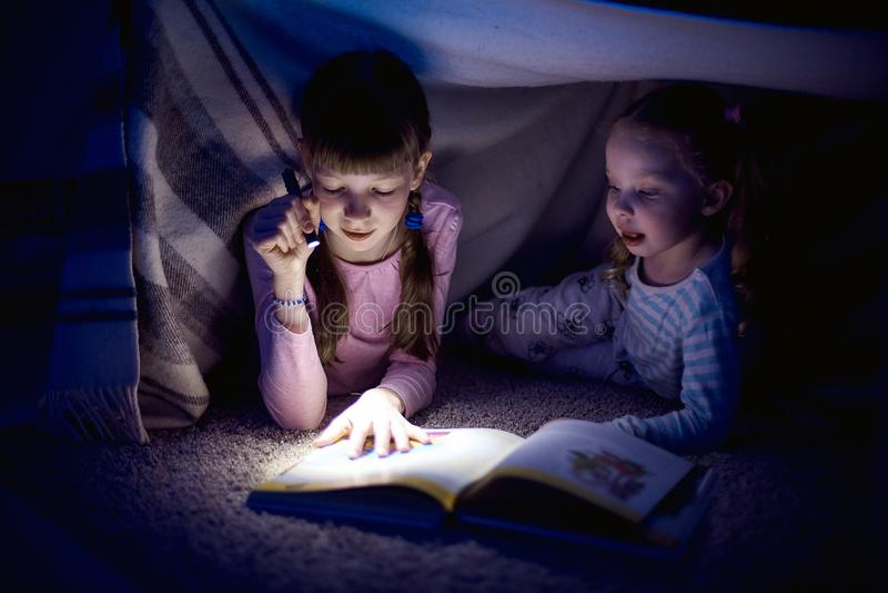 Twee zusters die een boek met een flitslicht in een donkere ruimte lezen bij nacht stock afbeeldingen