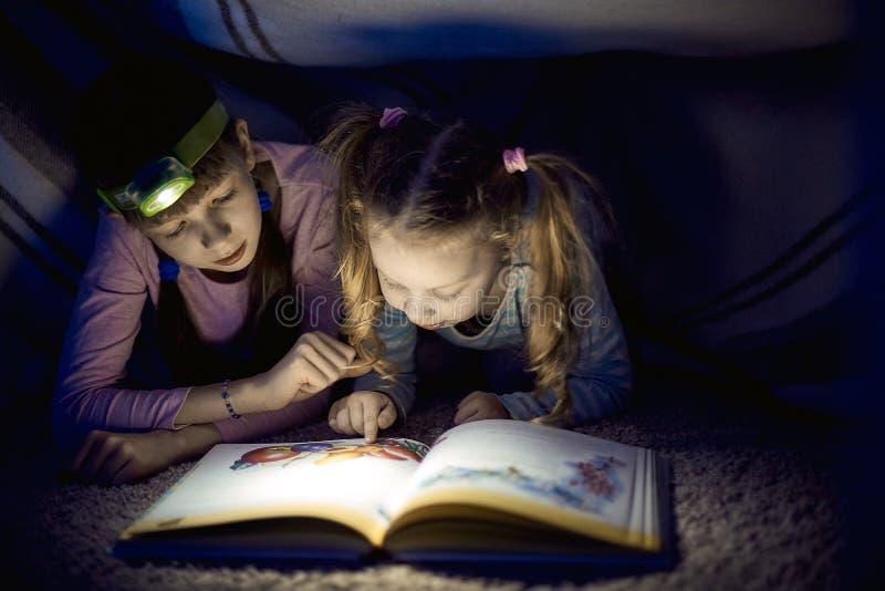 Twee zusters die een boek met een flitslicht in een donkere ruimte lezen bij nacht royalty-vrije stock afbeelding
