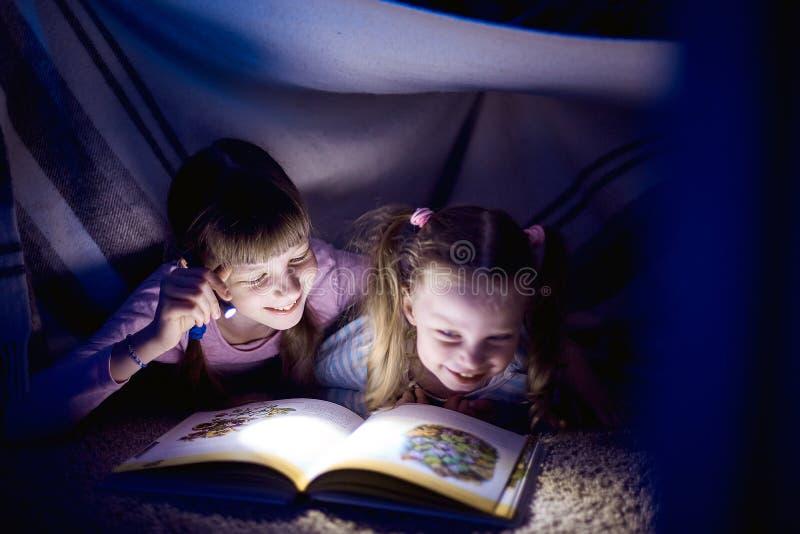 Twee zusters die een boek met een flitslicht in een donkere ruimte lezen bij nacht stock afbeelding