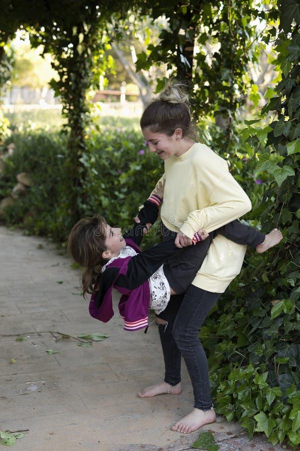 Twee zusters die in een tuin spelen stock afbeeldingen