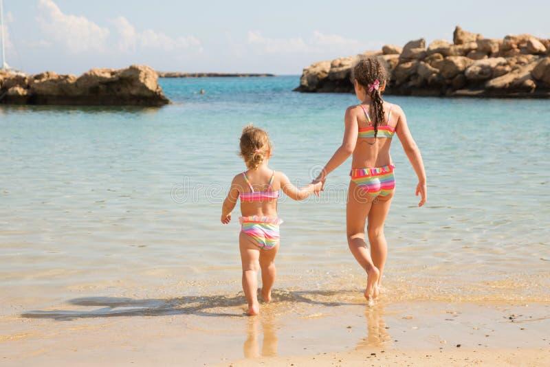 Twee zusters die handen houden en op het strand spelen royalty-vrije stock afbeelding