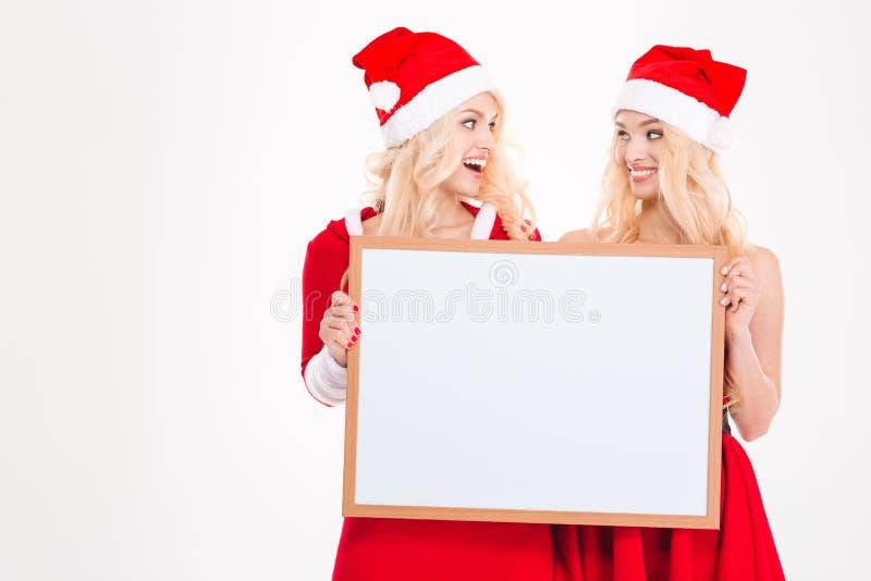 Twee zusters die lege raad houden en op elkaar kijken royalty-vrije stock afbeeldingen
