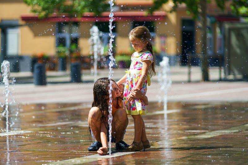 Twee zusters die met fontein spelen bespatten stock fotografie