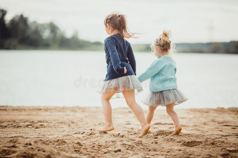 Twee zusters die op de kust van het meer spelen stock fotografie