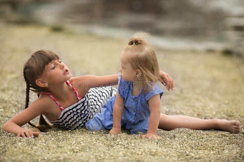 Twee zusters die op het strand spelen stock afbeeldingen