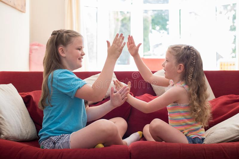 Twee Zusters die op Sofa Playing Clapping Game Together zitten royalty-vrije stock foto