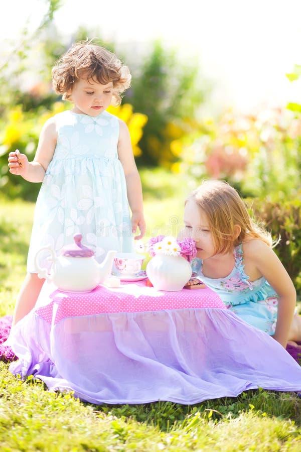 Twee zusters die theekransje in openlucht spelen stock foto's