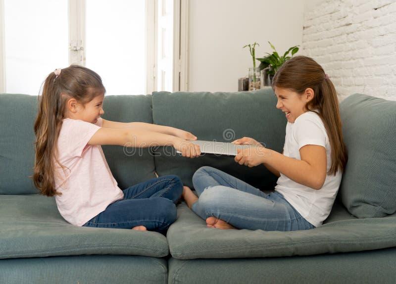 Twee zusters die voor laptop computer vechten Kinderen en technologieverslaving royalty-vrije stock foto's