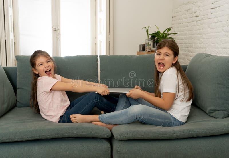 Twee zusters die voor laptop computer vechten Kinderen en technologieverslaving royalty-vrije stock afbeeldingen