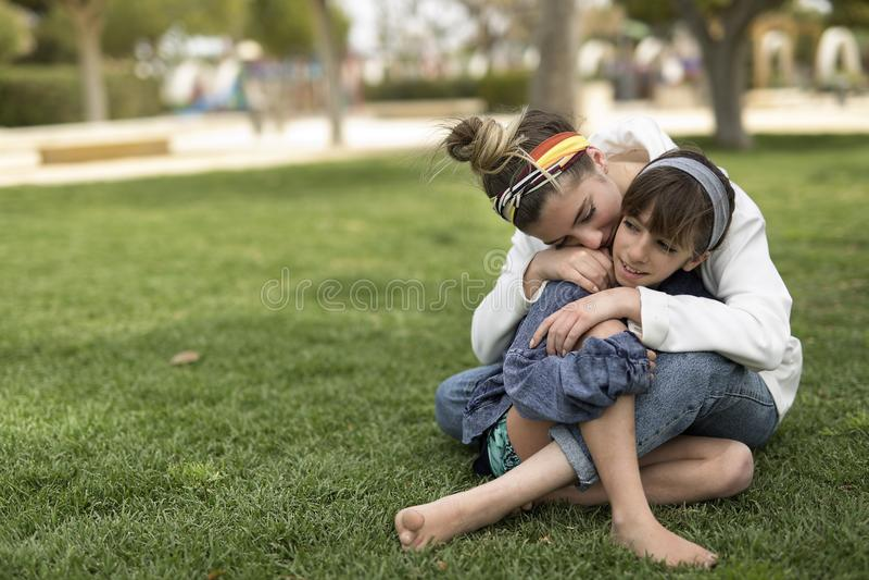 Twee zusters die zitting die van elkaar houden stock foto