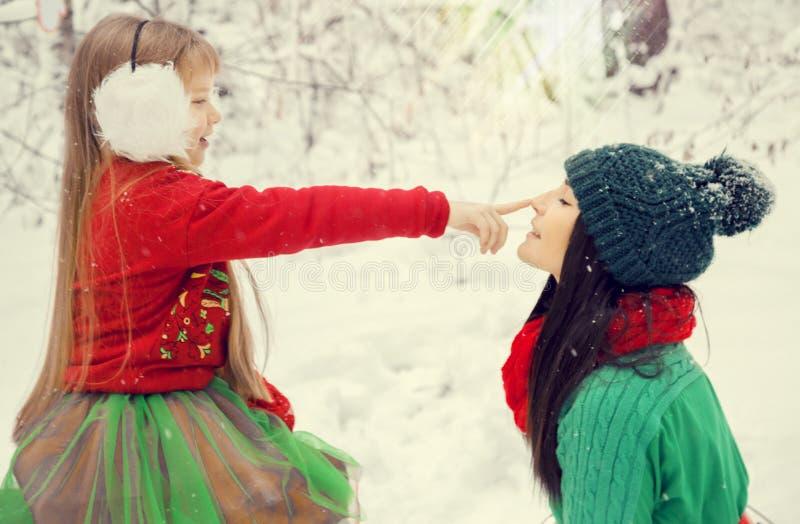Twee zusters, een klein meisje en haar oudere zuster die in kostuums van bloemen typisch van de elf van Kerstman` s helpers lopen stock afbeelding