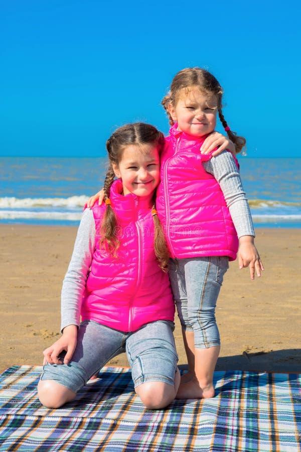 Twee zusters koesteren op het strand royalty-vrije stock fotografie