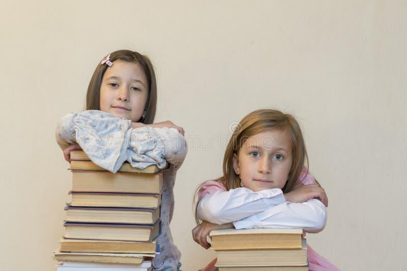 Twee zusters met een stapel van boeken op de vloer in de ruimte Het concept onderwijs en ontwikkeling van kinderen Liefde van royalty-vrije stock foto's