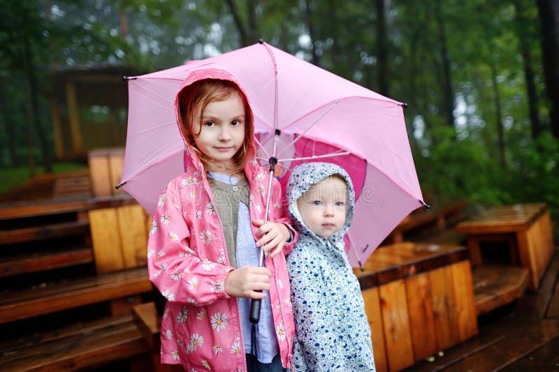 Twee zusters onder paraplu stock afbeeldingen