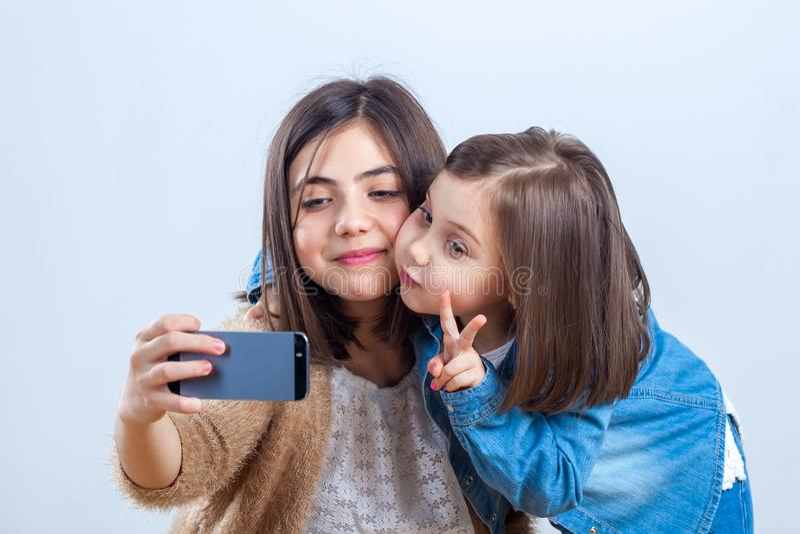 Twee zusters van verschillende leeftijden nemen een selfie in een fotostudio stock afbeelding