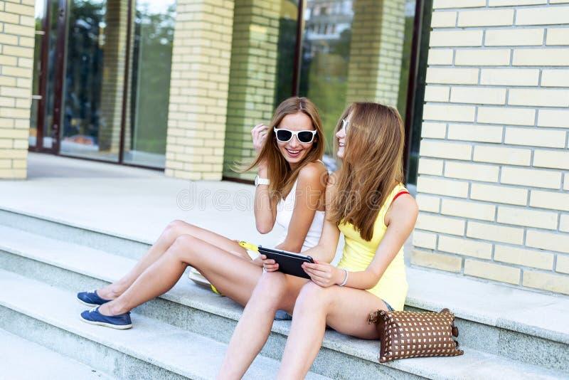 Twee zustersstappen van het instituut lachen gelukkig lettend op een filmtablet in sociale netwerkenglazen, rust, manier royalty-vrije stock afbeelding