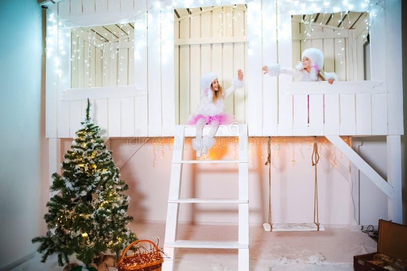 Twee zusterstweelingen in de kostuums van hondpoedels voor het Nieuwjaar Meisjes die op de portiek van een witte blokhuis verfraa royalty-vrije stock foto's