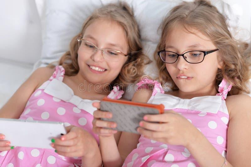 Twee zusterstweelingen die slimme telefoons met behulp van royalty-vrije stock afbeelding