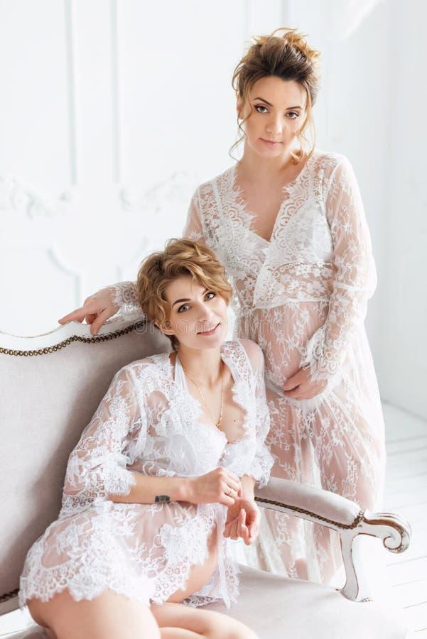 Twee zwangere meisjes die kantkleding in witte studio dragen royalty-vrije stock afbeelding