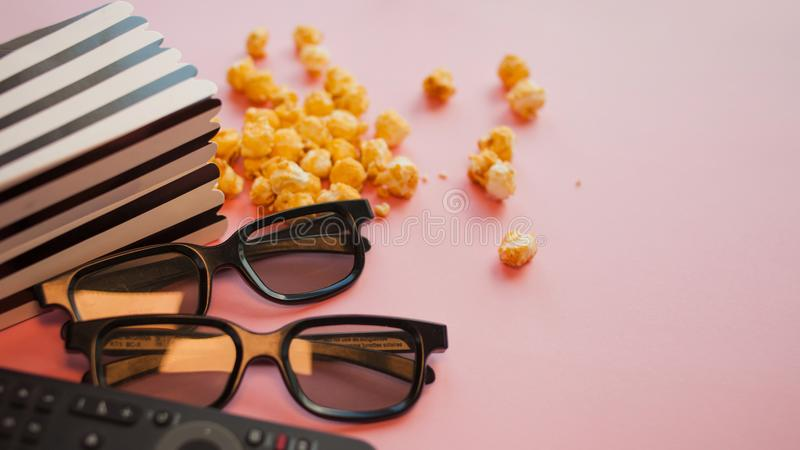 Twee zwarte 3d glazen liggen naast een zwart-witte papper gestreepte doos popcorn en TV-afstandsbediening royalty-vrije stock afbeeldingen
