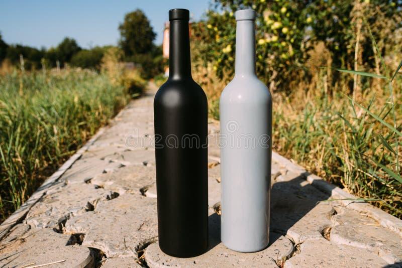 Twee zwarte en grijze flessen op de weg van de tegels, het dorp, landelijk alcoholisme, dronkenschap alcoholische ziekte natuurli royalty-vrije stock foto's