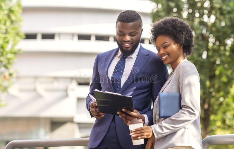 Twee zwarte glimlachende medewerkers die financiële verslagen controleren in openlucht, vrouw die koffie hebben stock foto's