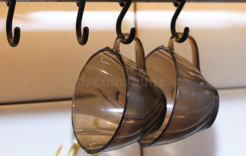 Twee zwarte koffiekoppen die op haken hangen royalty-vrije stock afbeelding
