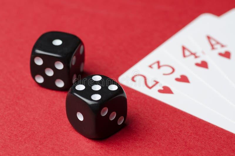 Twee zwarte kubussen en speelkaarten op een rode achtergrond stock foto's