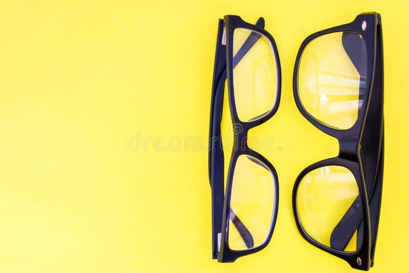 Twee zwarte oogglazen op gele eenvormige mening als achtergrond van hierboven met het duidelijke gebied van halve foto voor etike royalty-vrije stock afbeeldingen