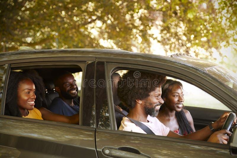 Twee zwarte volwassen paren in een auto tijdens een wegreis stock foto's