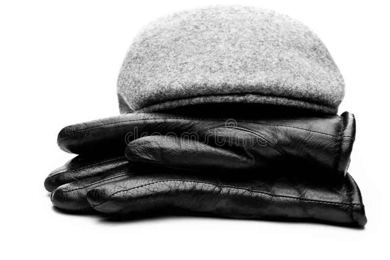 Tweed grey cap black leather gloves white background royalty free stock photography