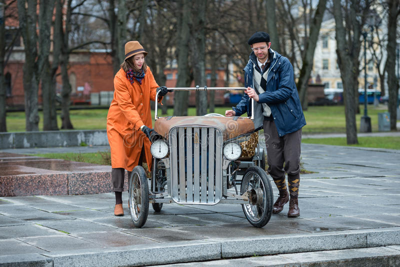 Tweed ride 2017. Unknown people on the stairs pushing a unique home-made bicycle mobile. stock images