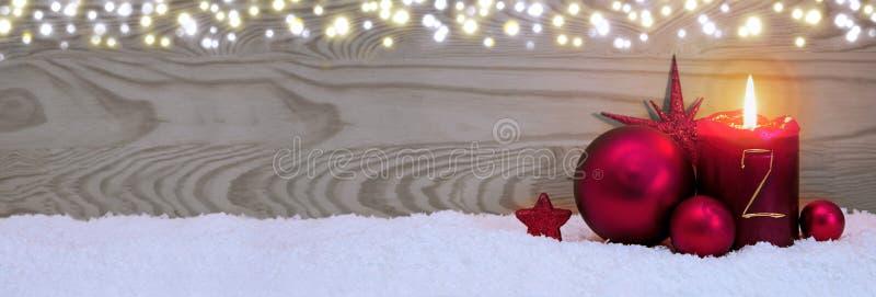 Tweede komst Kerstmisachtergrond met kaars en rode snuisterij stock foto's