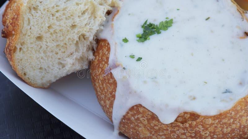 Tweekleppig schelpdiervissoep in de kom van het zuurdesembrood wordt en met kruiden wordt versierd gediend die dat stock foto
