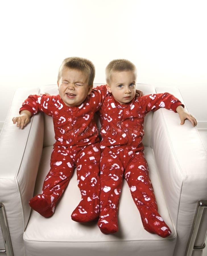 Tweeling jongens die samen zitten. stock afbeelding