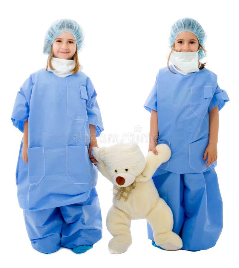 Tweeling kinderen artsen met teddybeer stock afbeelding